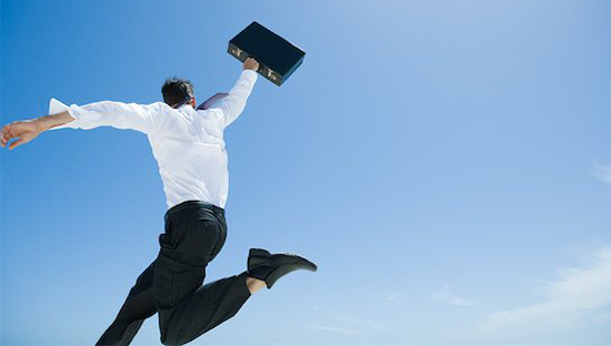 633-01574617 Model Release: Yes Property Release: No Businessman jumping in air with briefcase held up high, sky in background, low angle view